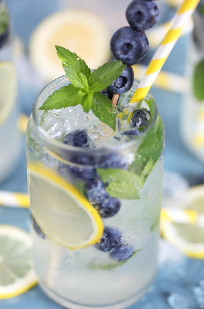 Close up of Lemonade Gin Mojito cocktail on a blue background.