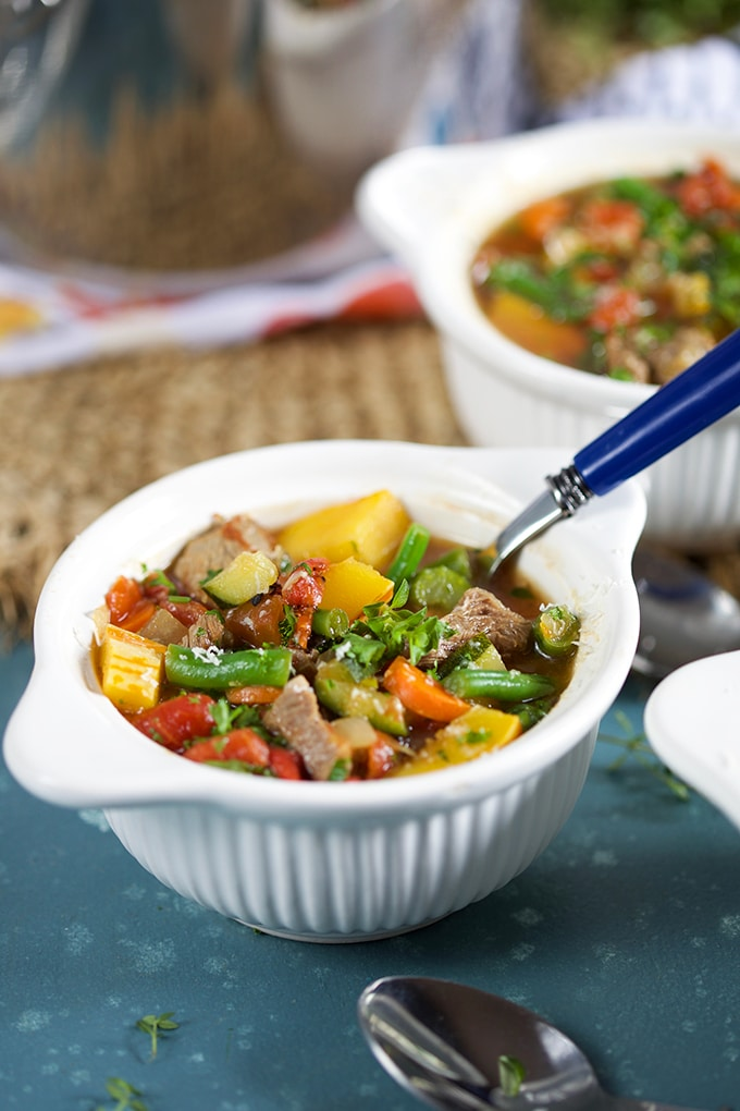 Vegetable Beef Soup in a white bowl with a blue handled spoon.