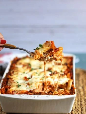 The Very Best Baked Ziti recipe in a white baking dish with a spoonful being scooped out and stretchy melty cheese from thesuburbansoapbox.com