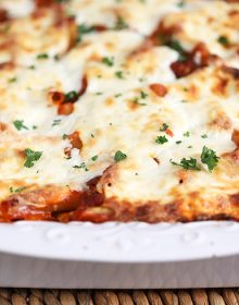 The BEST Baked Ziti in a white casserole on a wicker placemat from TheSuburbansoapbox.com