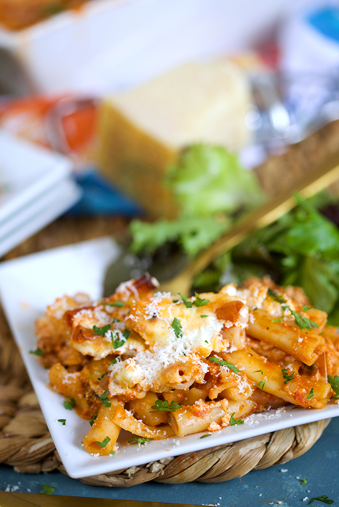 Close up shot of baked ziti recipe on a white square plate and a green salad with a gold fork from thesuburbansoapbox.com