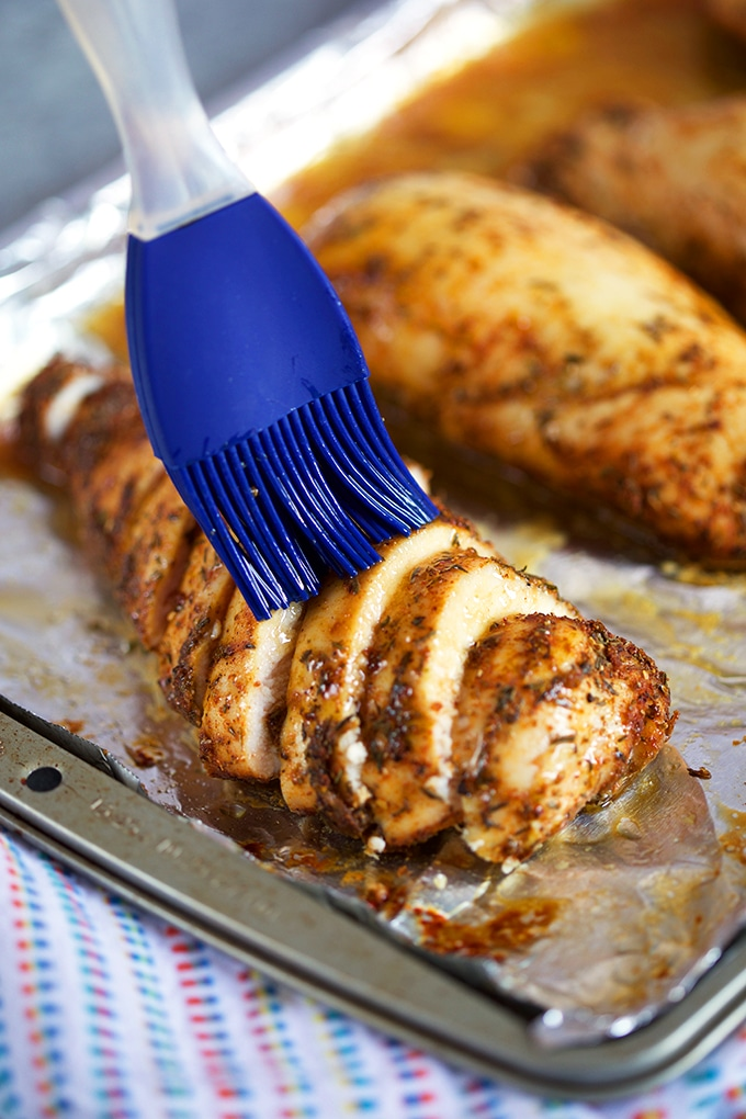 Sliced baked chicken breast being basted with a blue silicone basting brush on a foil lined baking sheet.
