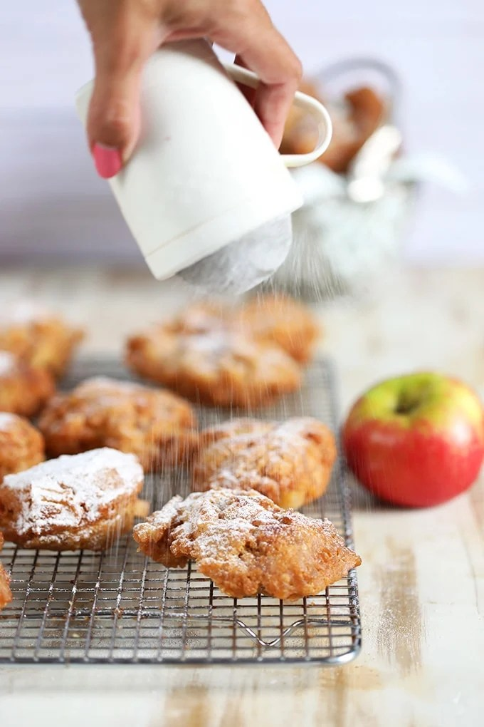 Apple fritters on a cooling rack with powdered sugar being dusted on top.