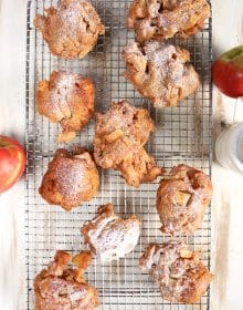 Apple fritters on a cooling rack on a rustic white background with apples from TheSuburbanSoapbox.com