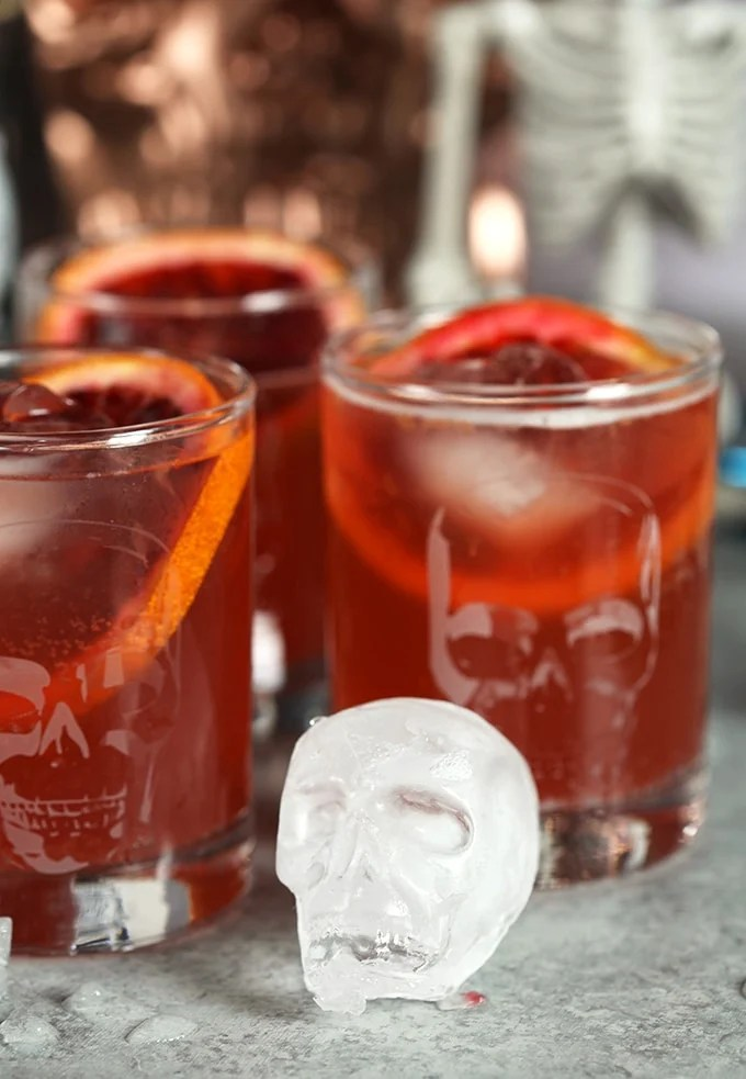Skull ice cube in front of three highball glasses filled with Dark and Stormy cocktails.