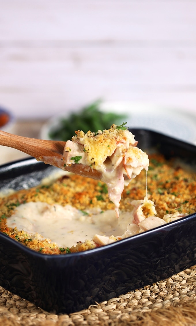 Chicken Cordon Bleu Casserole in a blue baking dish with a spoon serving it.