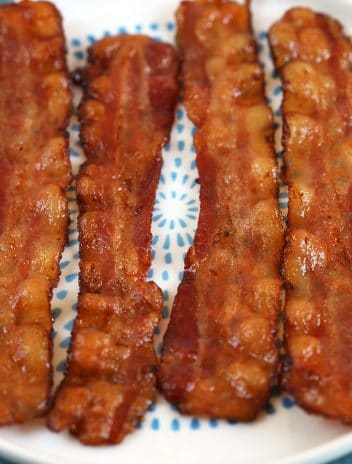 Four sliced of bake bacon on a white plate with blue dots.