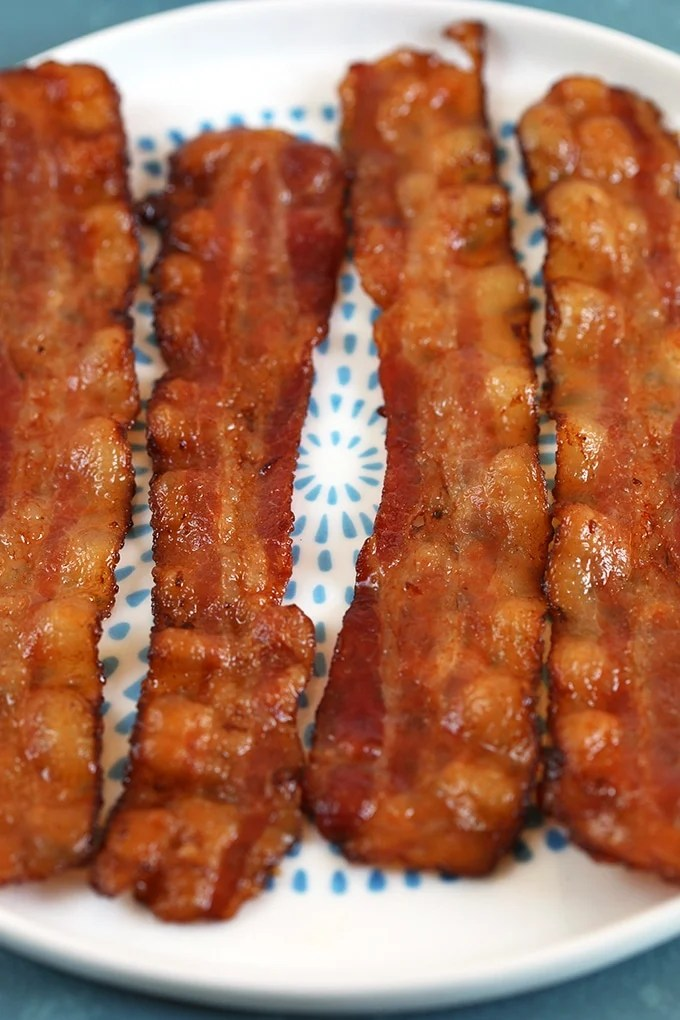 Four sliced of bacon on a white plate with blue dots.