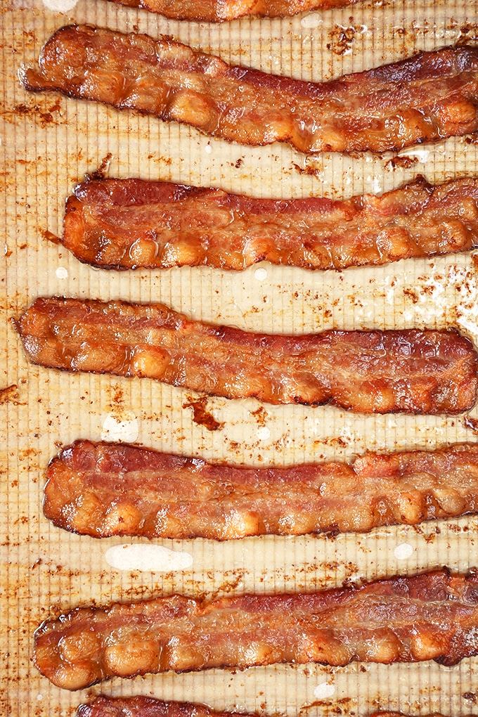 Baked bacon on a baking sheet with parchment.