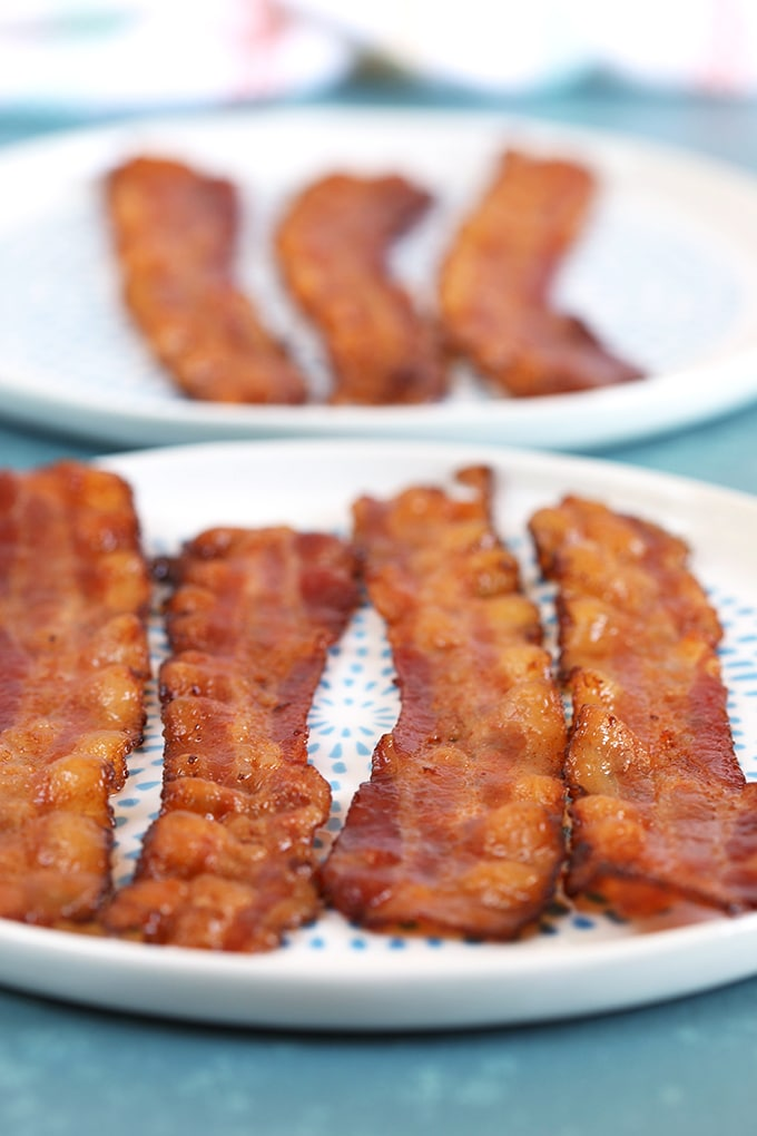 Bacon on a white plate with blue dots on a blue background.