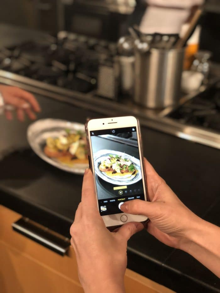 Photo of an iphone taking a picture of a chicken dish.