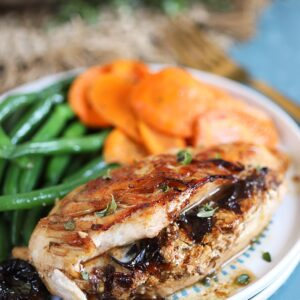 Prune Goat Cheese Stuffed Chicken on a white plate with green beans and carrots.
