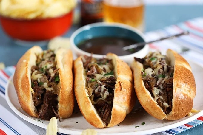 Three Slow Cooker French Dip Sandwiches arranged in a row on a platter with a bowl of au jus in the back
