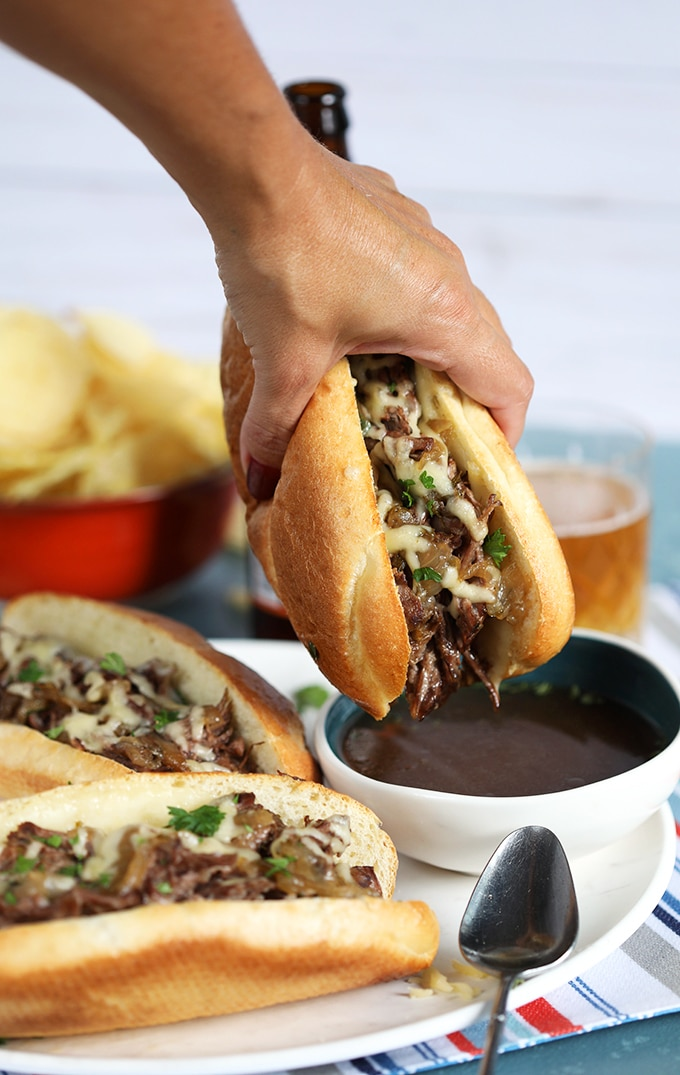 Slow Cooker French Dip Sandwich being dipped into a bowl of au jus on a blue background from TheSuburbansoapbox.com