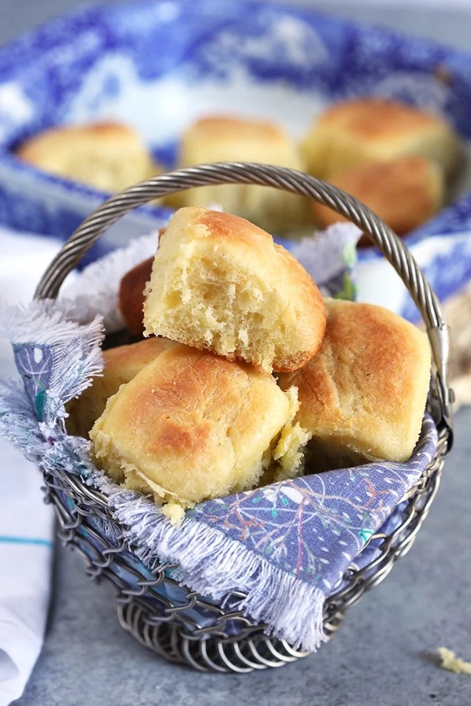 Dinner rolls in a basket with blue linens.