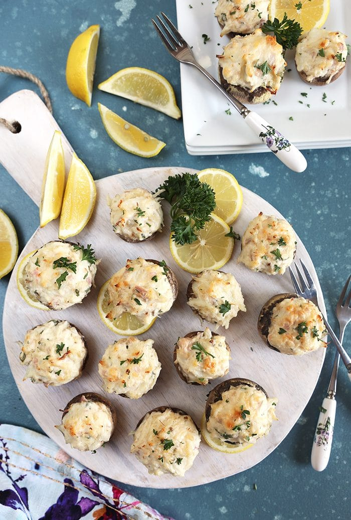 Overhead shot of crab stuffed mushrooms on a white board with lemons and parsley.