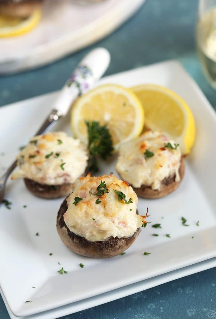 Close up shot of Crab Stuffed Mushrooms on a square plate with lemons and a fork.