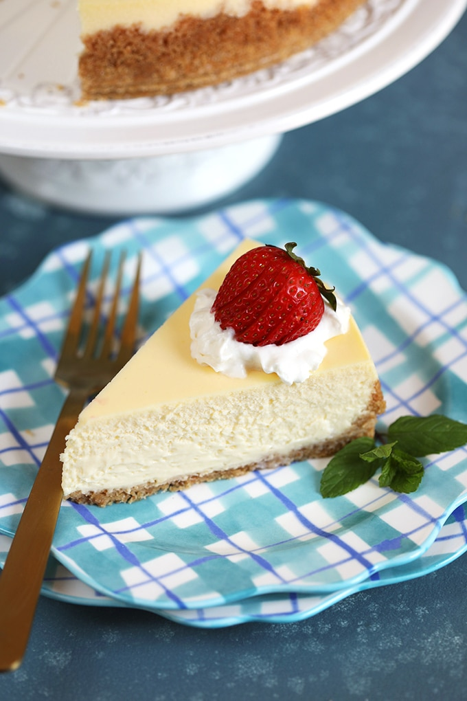 Slice of New York Cheesecake on a blue plaid plate with a gold fork.