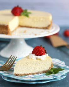 New York Cheesecake slice on a blue plaid plate with the whole cake in the background on a white cake plate.