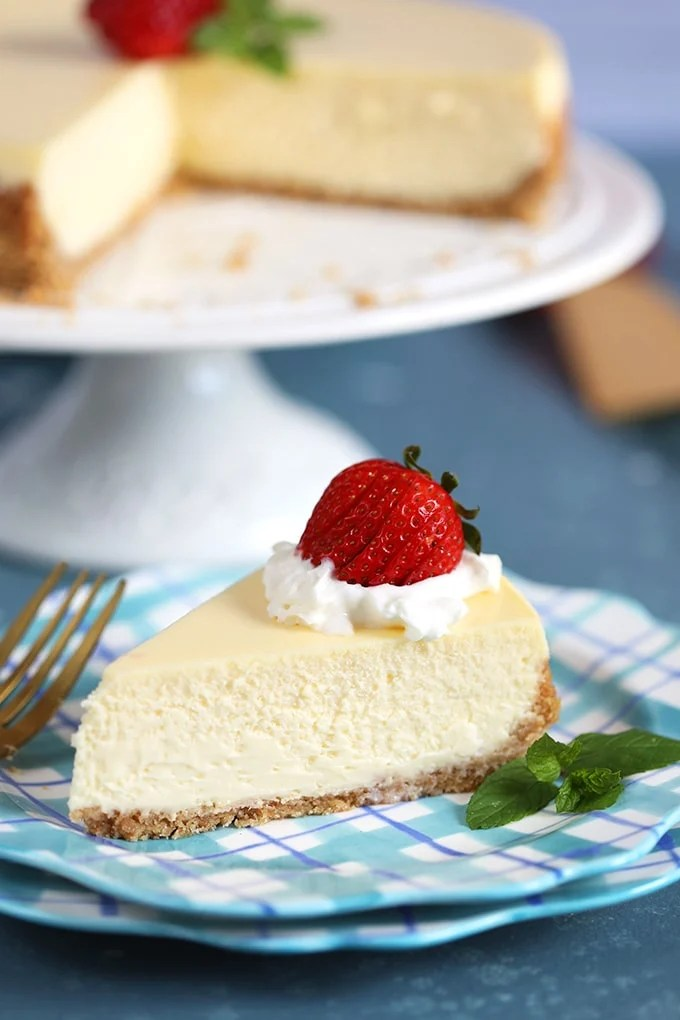 A slice of New York Cheesecake on a blue plaid plate with a strawberry and whipped cream on top and a sprig of mint.