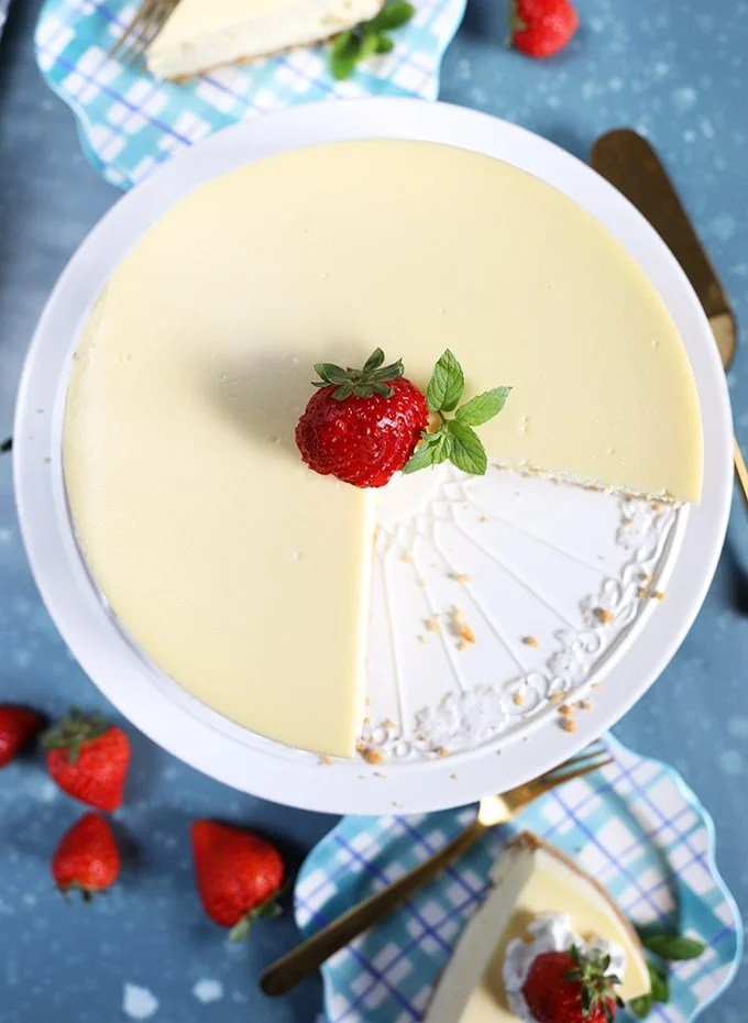 overhead shot of New York cheesecake with a slice cut out on a white cake plate with a strawberry in the center.