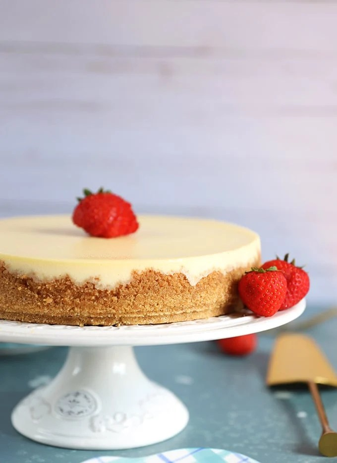 Whole New York Cheesecake on a white cake plate on a blue background.