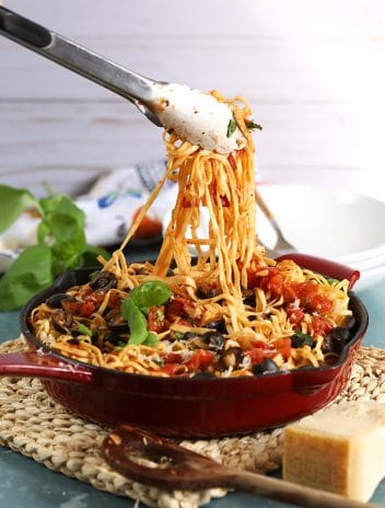Pasta Puttanesca in a red skillet with tongs lifting pasta out of the pot.