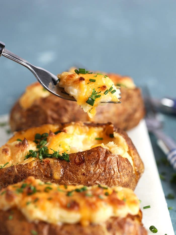 Close up of twice baked potatoes with a fork taking a bite.