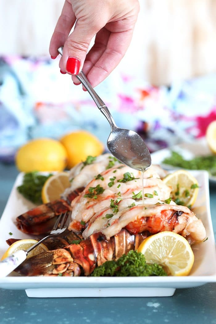 Lobster Tails on a white platter with a silver spoon drizzling melted butter over top.