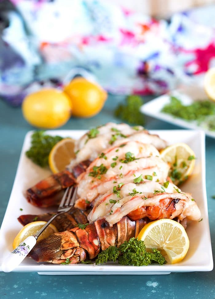 Baked lobster tail on a white platter with lemon and parlsey.