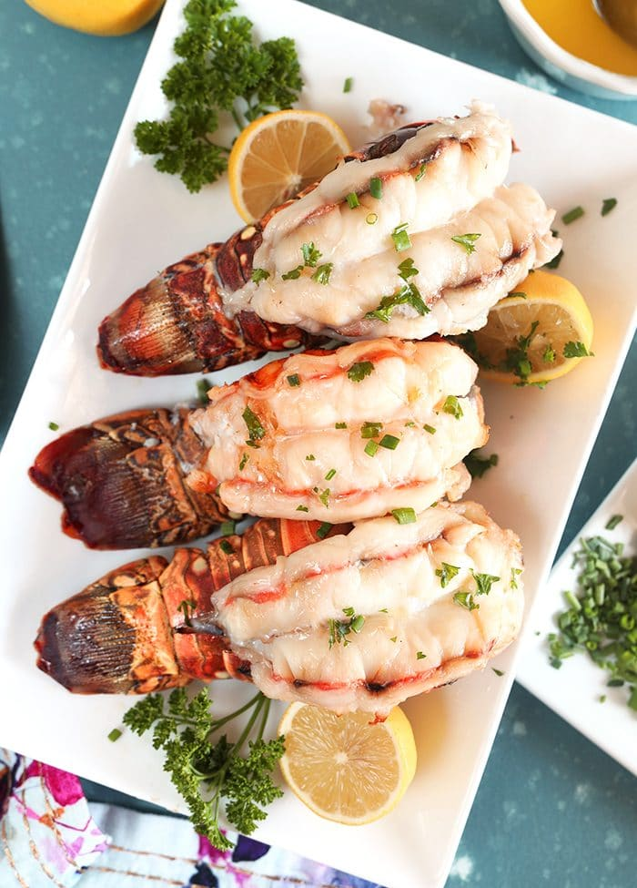 Overhead shot of three baked Lobster Tails with lemons and parsley on a white platter.