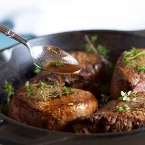 Filet Mignon in a cast iron skillet with pan juices being spooned over the steaks.