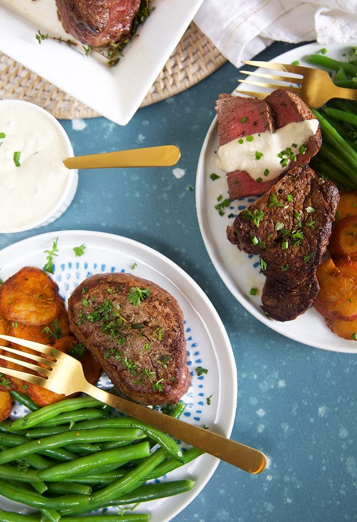 Overhead shot of filet mignon on a white plate with green beans and a gold fork.