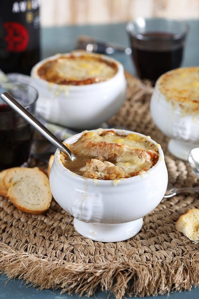 Baked French Onion Soup on a straw placemat in a white crock with a silver spoon in the bowl.