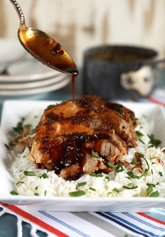 Honey garlic sauce being drizzled over Slow Cooker Pork Loin Roast on a bed of white rice.