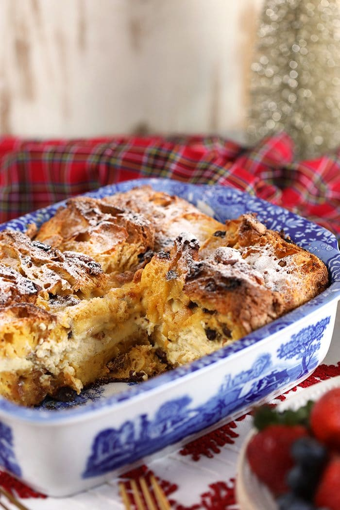 Panettone French Toast Casserole in a blue and white casserole dish with a plaid napkin in the background.