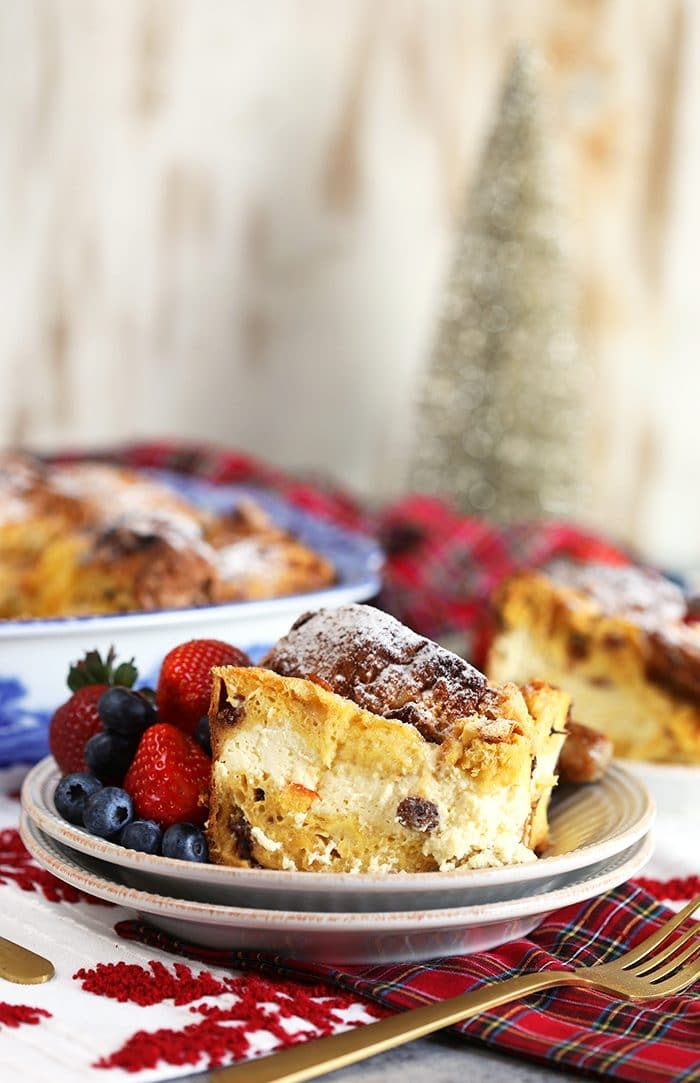 Cheesecake Stuffed Panettone French Toast Casserole on a white plate with plaid napkin.