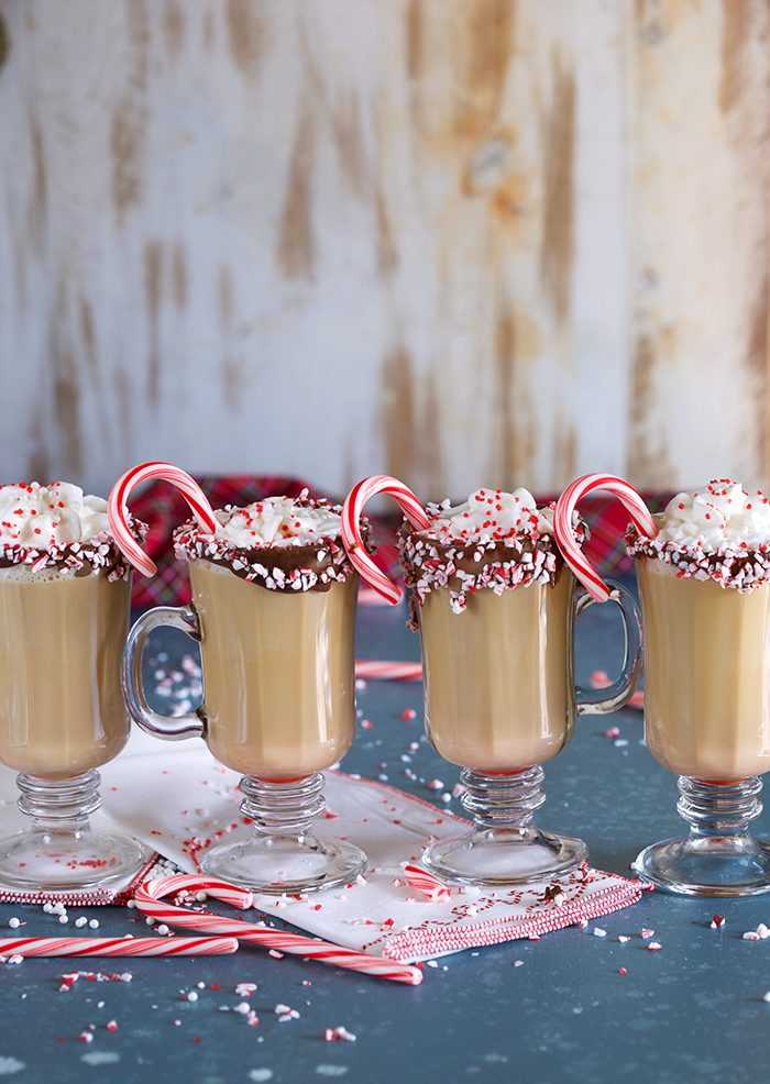 A row of Spiked Peppermint Mocha coffees in a glass mug on a blue background with candy canes and sprinkles.
