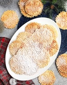 Overhead shot of platter of pizzelles on a gray background with bottle brush trees and a plaid napkin.