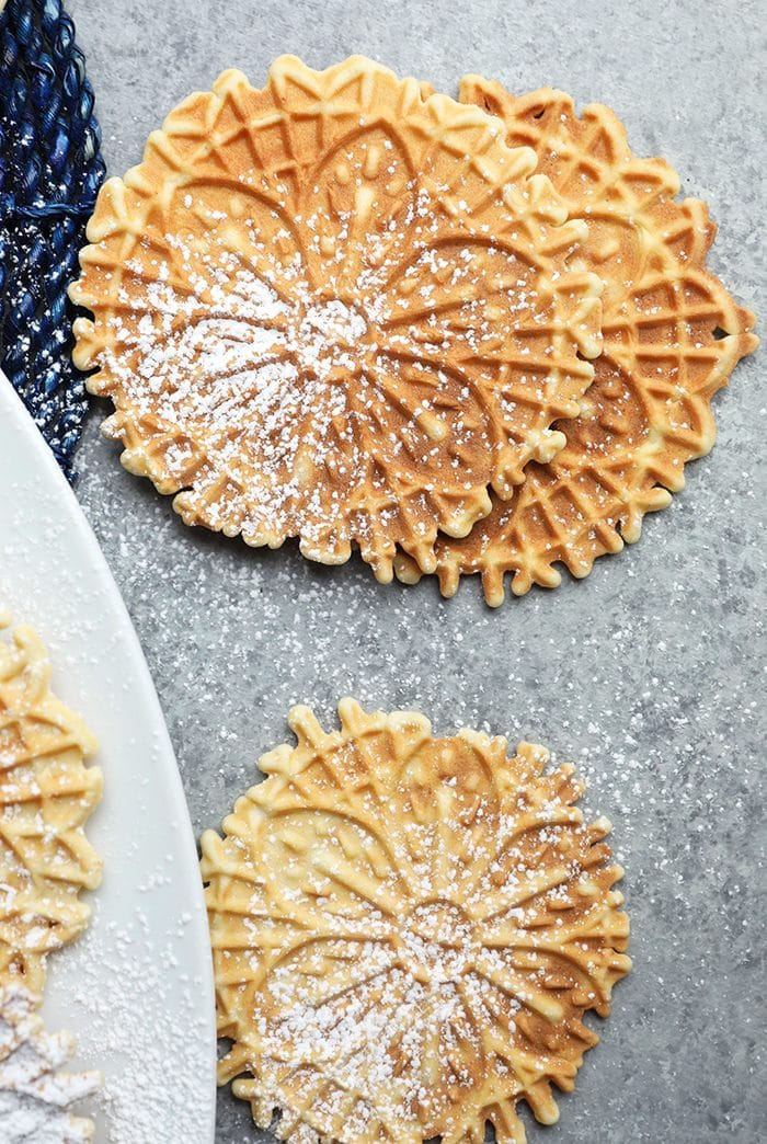 Close up of Pizzelles on a gray background.