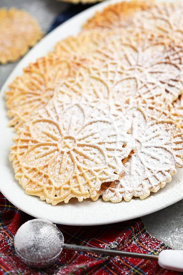 Homemade Pizzelles on a white platter with a plaid napkin underneath.