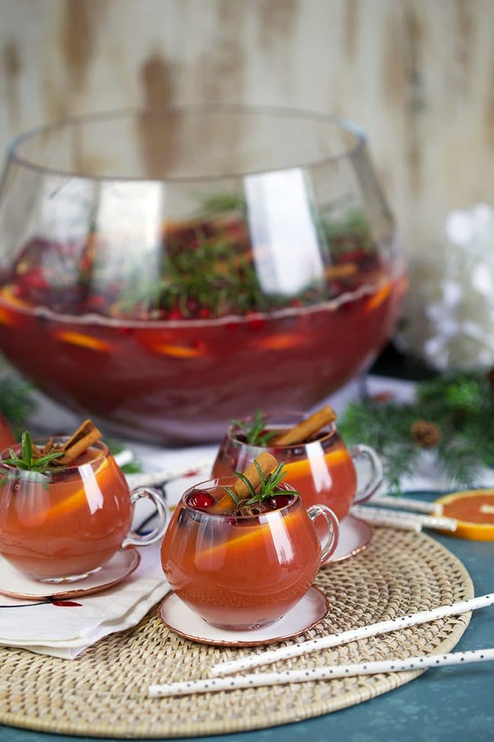 Three glasses sparkling pomegranate rum punch with cranberry, rosemary and orange slices.