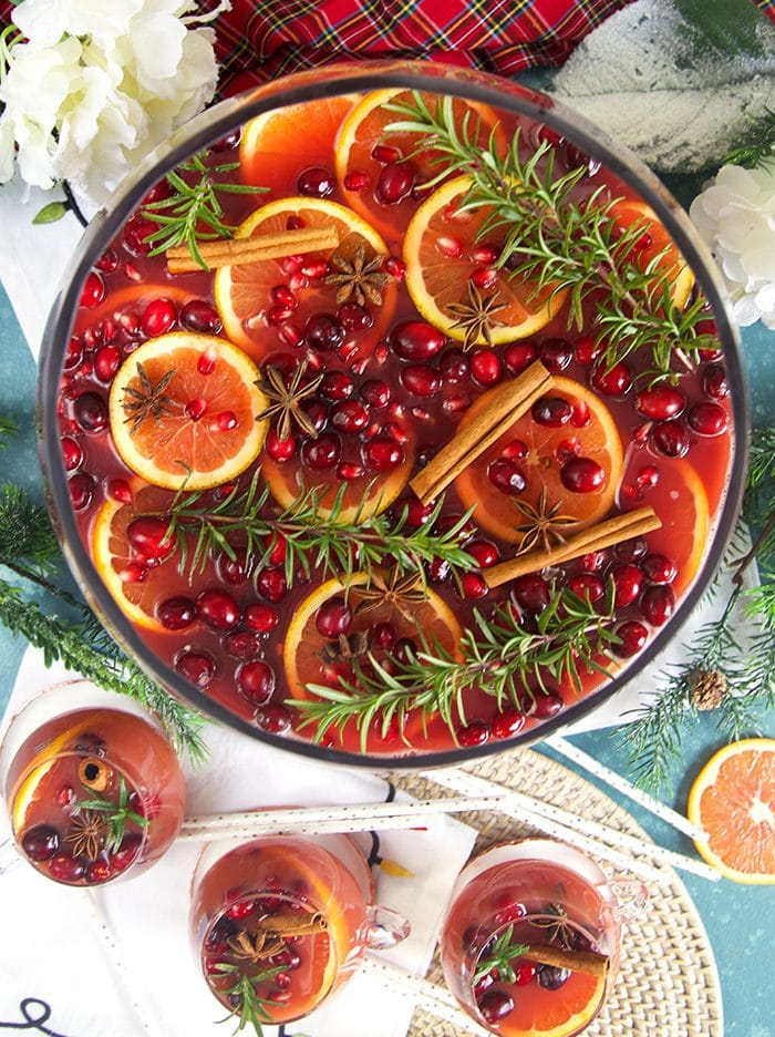 Overhead shot of sparkling pomegranate rum punch with orange slices rosemary cranberries and white napkin under neath.