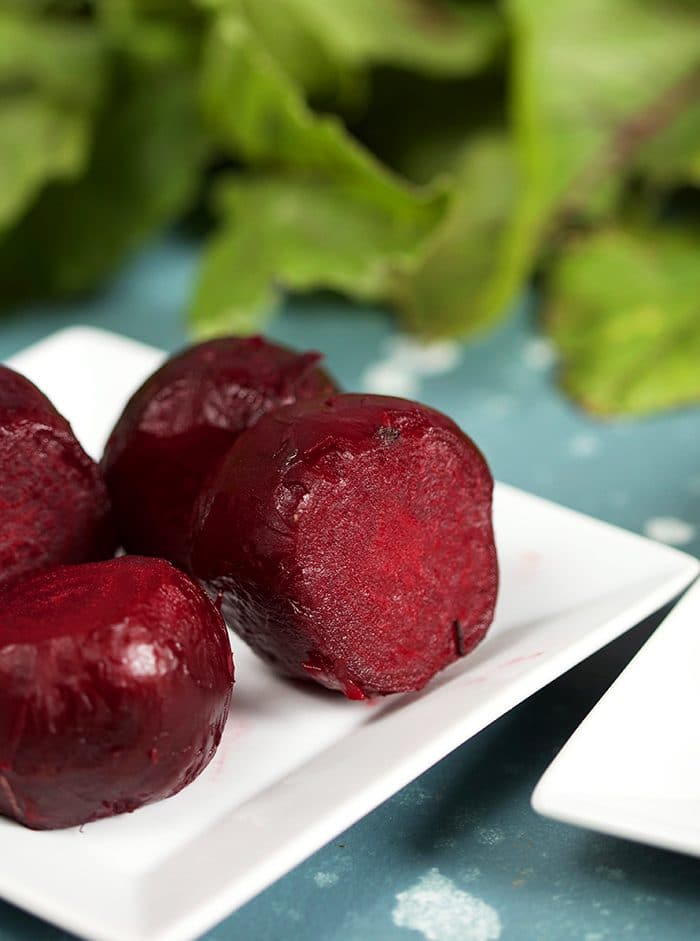 Oven Roasted Beets on a white square plate with beet greens in the background.