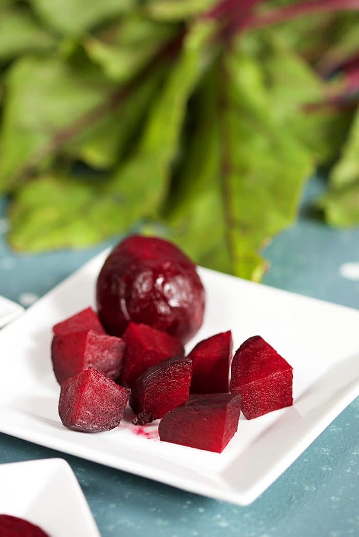 Diced Roasted Beets on a white square plate with beet greens in the background.