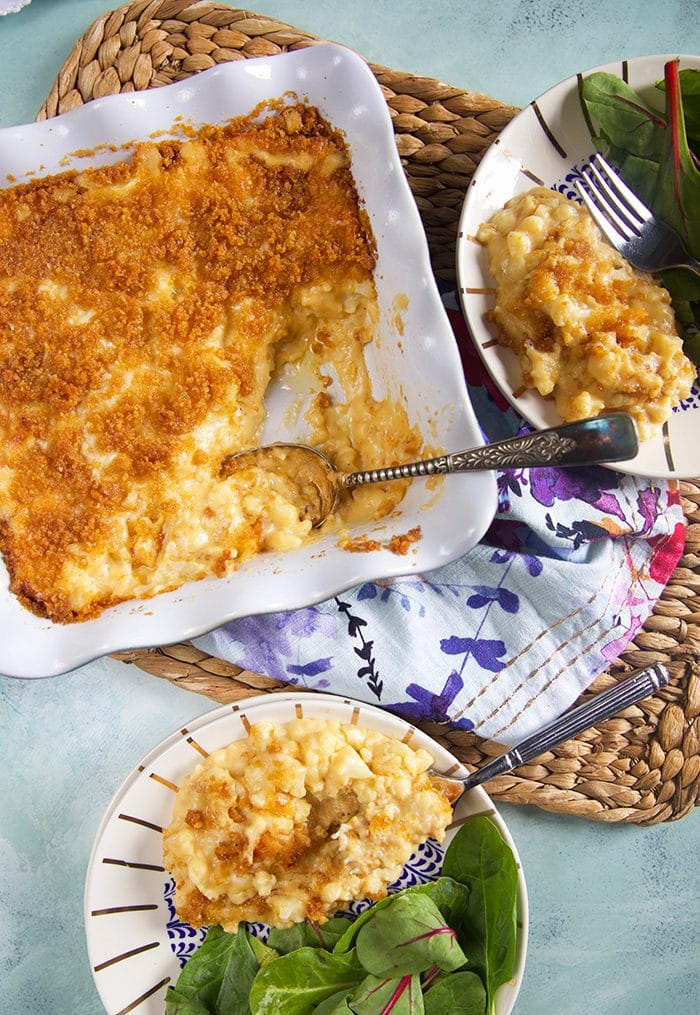 Overhead shot of Cauliflower Mac and Cheese in a white baking dish with a spoon in them.
