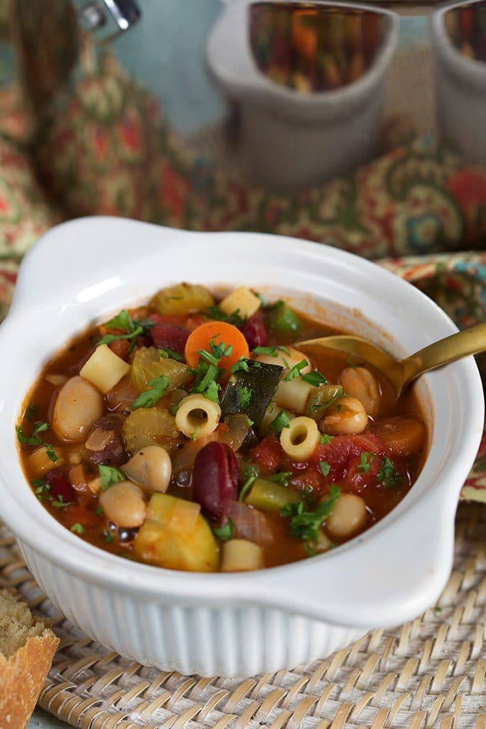 Close up of white bowl with minestrone soup on a wicker placemat.