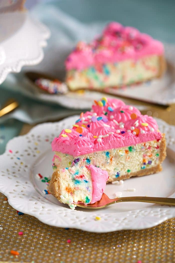 Funfetti Cheesecake recipe with a fork on a plate with a bite ready to eat.