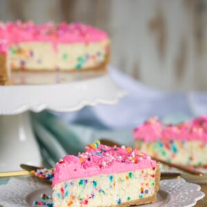 Funfetti Cheesecake with hot pink whipped cream frosting on a white cake plate with a slice of cheesecake on a white plate.
