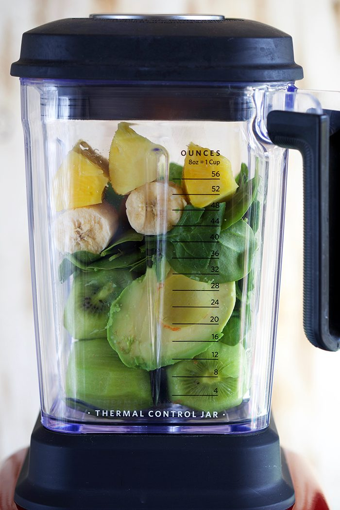 Kiwi Pineapple Spinach Smoothie ingredient in the pitcher of a blender.